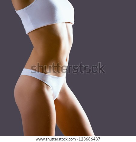 Body of young and beautiful woman isolated on gray background