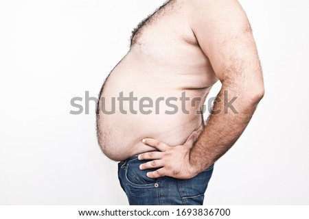 Body part of asian fat man with a big hairy belly. overweight man closeup of belly side view - Man touching his fat belly - fat man & Diet, Belly Fat. isolated on white background. Unhealthy Lifestyle
