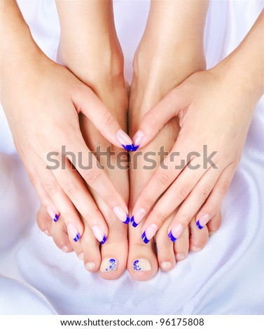 body part shot of beautiful healthy young woman's hands and legs with manicured fingers and pedicured toes on silk cloth