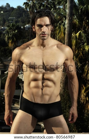 Body portrait of a sexy male fitness model in black briefs with muscular chest and six pack abs against lush outdoor background