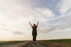 Body positive, freedom, high self esteem, confidence, happiness, inspiration, success, positive affirmation. Overweight woman celebrating rising hands to the sky on summer meadow.