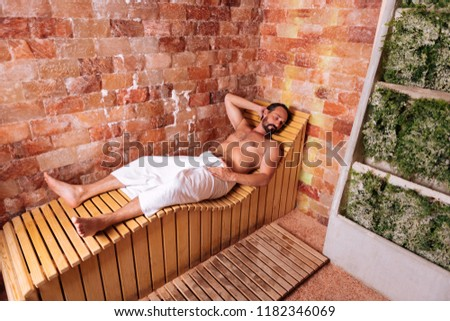 Body relaxation. Pleasant good looking man lying on the wooden bench while relaxing in the sauna #1182346069