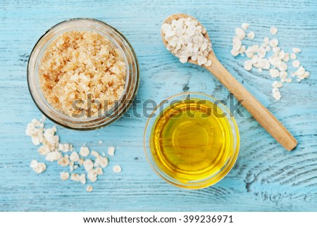 Body scrub of oatmeal, sugar, honey and oil in glass jar on blue rustic table, homemade cosmetic for peeling and spa care, top view