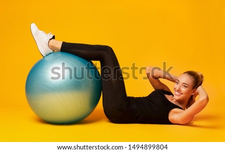 Body Shaping. Smiling Young Woman Doing Abs Exercise With Fitball On Yellow Studio Background.