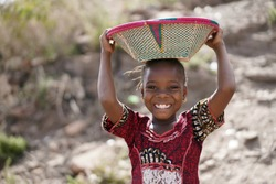 Body Shot of Cute African Young Girl Carrying Food Basket and Blurred Background