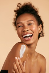 Body skin care. Smiling black woman applying body cream portrait. Beautiful happy african american girl model with cosmetic moisturizing lotion on perfect hydrated soft skin on shoulder at studio