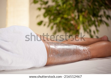 Body wrapping in a spa room, horizontal