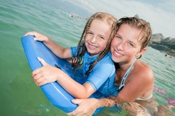 Bodyboarding - young girls surfing in the sea