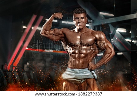 Bodybuilder athlet man pumping up muscles in the gym. Brutal strong muscular guy on fitness workout. Bodybuilding concept. Photo stock ©