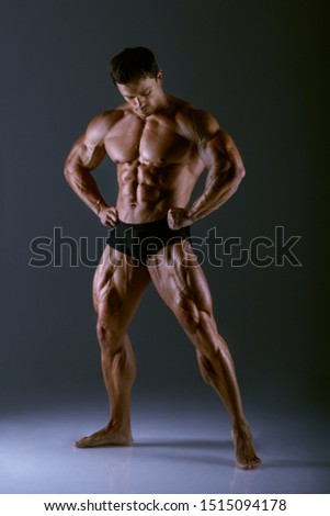 Bodybuilder athlete shows muscles in the studio on a dark background. Bodybuilder Posing. Bodybuilder training
