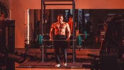 Bodybuilder athletic man with six pack, perfect abs, shoulders, biceps, triceps, chest. Barbells workout. Athletic guy standing with barbell, workout in gym. Muscular man workout with barbell at gym.