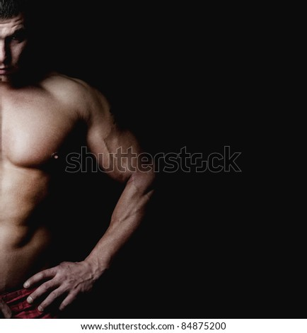 Bodybuilder demonstrates his muscular body. Isolated on black background.