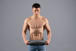Bodybuilder do muscle building workout with resistance band grey background, training.
