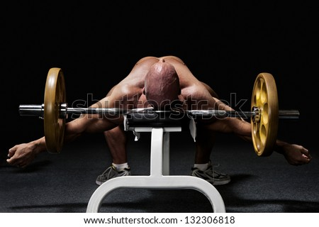 Bodybuilder lying exhausted on workout bench in gym with barbell from the back isolated on black