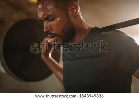 Bodybuilder man working out at gym with heavy weights. Fitness man doing back squats with barbell. Foto stock ©