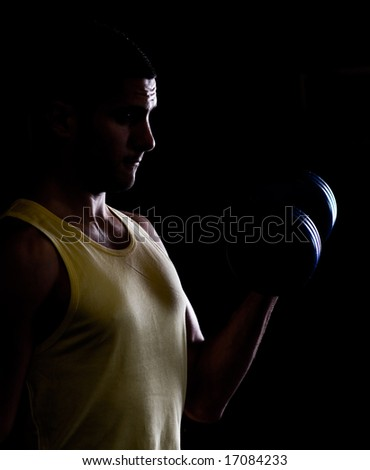 Bodybuilder Man working out in gym with dumbells