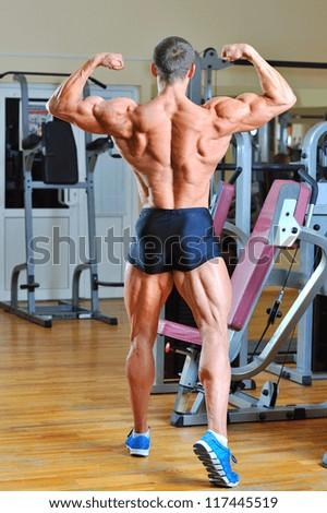 Bodybuilder posing at gym - back view full lenght portrait