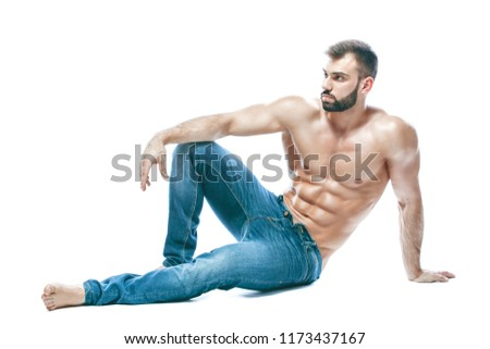 bodybuilder posing. Beautiful sporty guy male power. Fitness muscled in blue jeans. on isolated white background. sits on the floor
