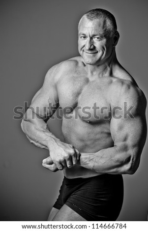 Bodybuilder posing in a room