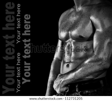 Bodybuilder posing on the black background - stock photo