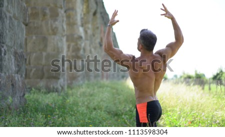Bodybuilder Posing Outside In Different Poses Demonstrating His Muscles - Male Showing Muscles #1113598304