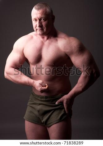 Bodybuilder posing over gray background