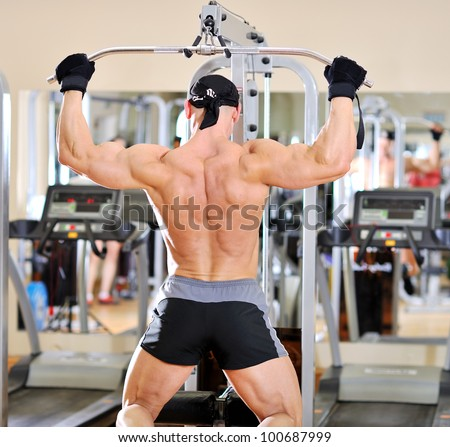 Bodybuilder shakes his back on the simulator. Back view