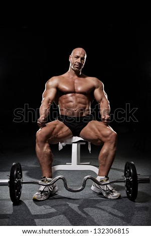 Bodybuilder sitting on workout bench in gym with barbell isolated on black