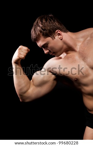 bodybuilder strong athletic man show muscle arm, sport guy showing his male muscles, over black background half body - stock photo