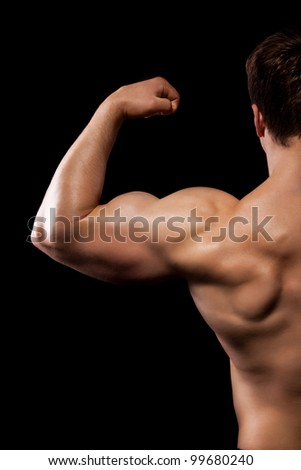 bodybuilder strong athletic man show muscle arm, sport guy showing his male muscles, standing back over black background, half body