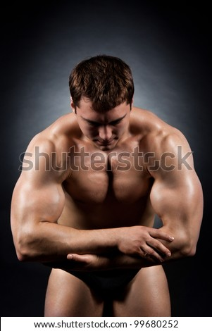 bodybuilder strong athletic muscle man, sport guy showing his male muscles, over black background