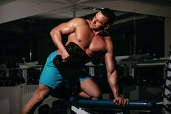 Bodybuilder training biceps in gym lifting dumbbells. Exercises and workout. Sportsman with shirtless torso