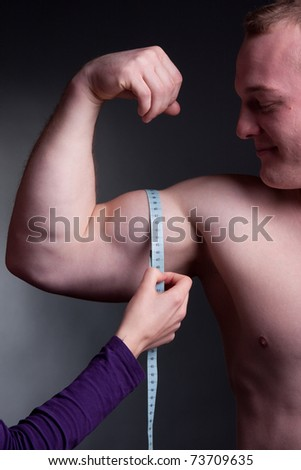 bodybuilder with a measuring tape around his bicep stock photo 73709635 shutterstock. Black Bedroom Furniture Sets. Home Design Ideas