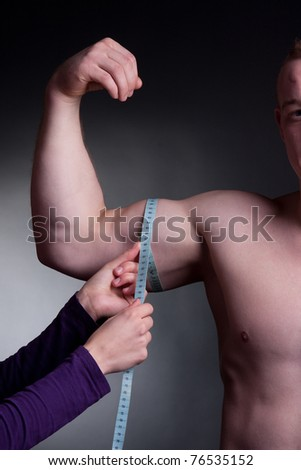 bodybuilder with a measuring tape around his bicep