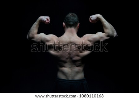 Bodybuilder with fit torso, back view. Man athlete flex arm muscles. Sportsman show biceps and triceps. Workout and training activity in gym. Sport power and bodycare concept. #1080110168