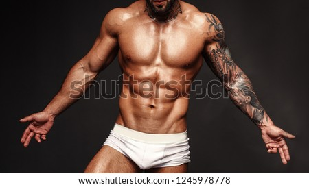 Bodybuilder with muscle torso. Banner image of sexy man with muscular body. Portrait of sexi male model. Hot macho in abs poses on black background. 16 in 9 crop for design.