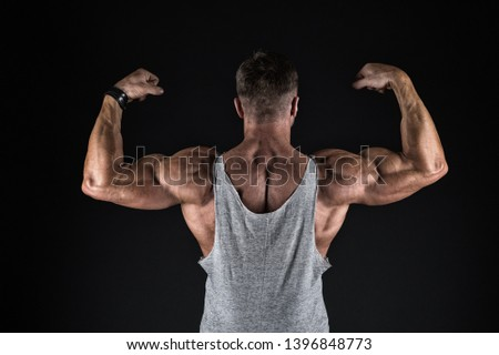 bodybuilding and sport. strength and shape concept. Sport and fitness. Bodybuilder showing muscles, biceps and triceps. flexing arms with fists. bodybuilding. bodybuilder show his muscles. body care.