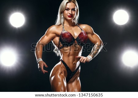 Bodybuilding competitions on the scene. Woman sportsmen and athlete. Black background with lights. Women's physique or bikini show on arena,