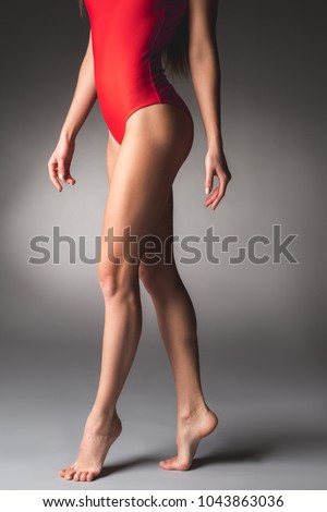 Bodybuilding concept. Well shaped female body with cared skin standing in red swimsuit. Close up of legs
