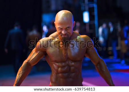 Bodybuilding contest behind the scenes: the contestant is preparing for the performance. Selective focus. #639754813