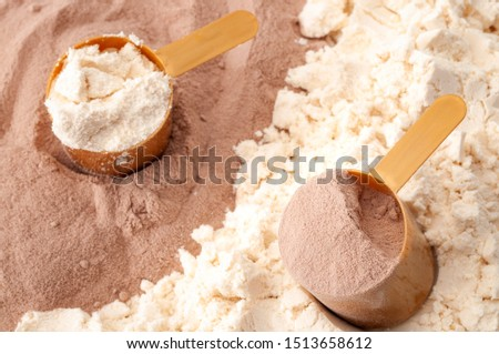 Bodybuilding diet, exercise nutrition, muscle mass growth and nutritious workout supplement conceptual idea with close up on two measuring scoops of casein and whey protein powder