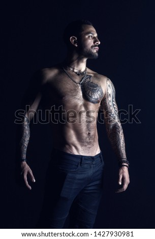 Bodycare with fitness and sport. Tattooed man show sexy muscular torso. Sportsman with six pack and ab. Bodybuilder with biceps and triceps. Fashion model with tattoo in jeans.
