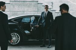 bodyguard in sunglasses opening car door to businessman