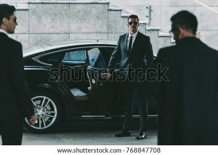 bodyguard in sunglasses opening car door to businessman Сток-фото ©