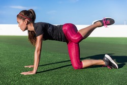 Bodyweight exercises - fitness woman doing fire hydrants legs kickbacks. Active girl training glute muscles raising one leg to the side and back for strength training in outdoor gym on grass floor.