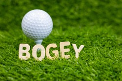 Bogey word with golf ball behind on green grass. one stroke over par a : one stroke over par on a hole made a bogey on the second hole