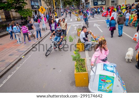 BOGOTA, COLOMBIA - FEBRUARY 9, 2015: Unidentified hispanic pedestrians, cyclists, dogs and food vendors moving through city street Candelaria area Bogota