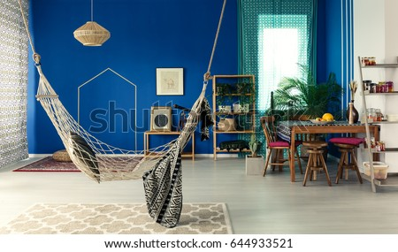 Bohemian apartment with blue wall, hammock, pattern rug, dining table