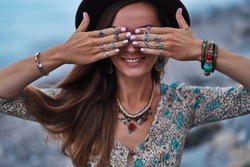 Bohemian chic gypsy smiling happy free woman with manicure wearing hands jewelry accessories, felt hat and dress. Boho detail close up