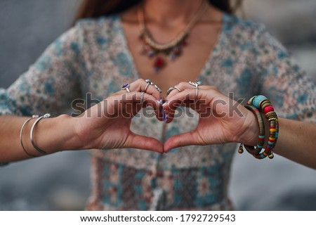 Bohemian chic gypsy woman wearing hands jewelry accessories and dress showing love sign. Boho detail close up   Foto d'archivio ©